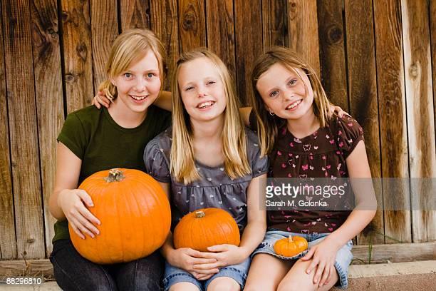 Girls holding pumpkins