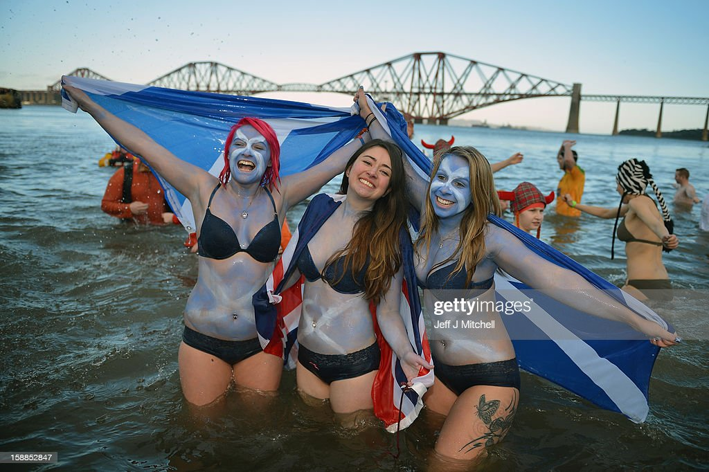 Girls holding saltire flags join around a thousand New Year swimmers, many in costume, who braved freezing conditions in the River Forth in front of the Forth Rail Bridge during the annual Loony Dook Swim on January 1, 2013 in South Queensferry, Scotland. Thousands of people gathered last night to see in the New Year at Hogmanay celebrations in towns and cities across Scotland..