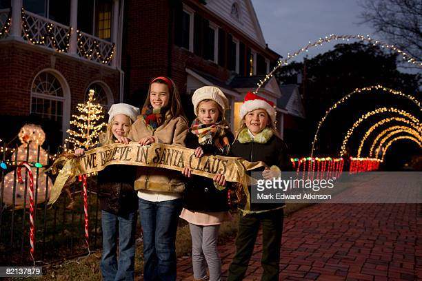 Girls holding Santa Claus banner