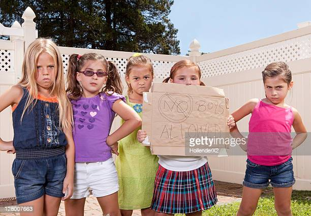 girls holding sign 'no boys allowed'