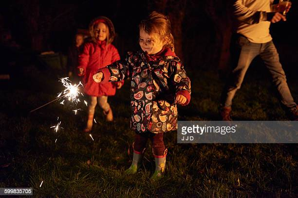Girls holding sparklers smiling