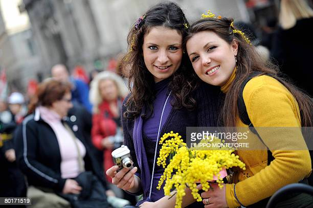 Girls holding typical Woman's day mimosa flowers attend Italy's three largest trade unions Cgil Cisl and Uil national rally in Rome's Piazza Navona...