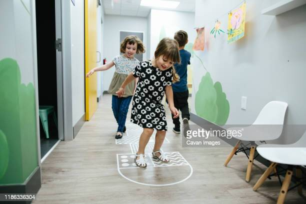 girls hopscotch together inside an educational facility - calabasas stock pictures, royalty-free photos & images