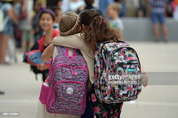 Girls hug each other outside the European school of Strasbourg in Strasbourg eastern France on September 1 the first day of the new school year AFP...
