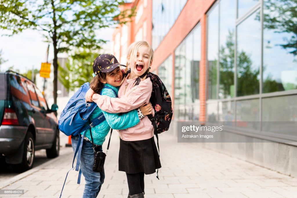 Girls (8-9) hugging and laughing by school : Foto de stock