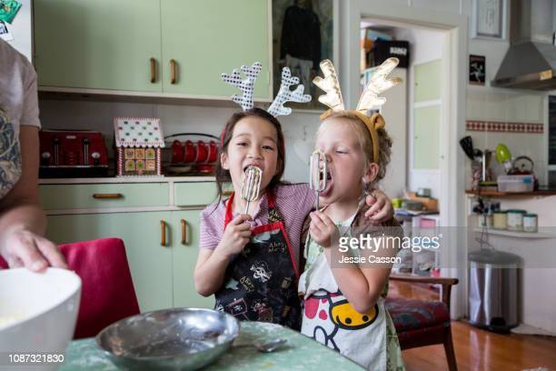 girls hugging and tasting mix from egg beater whilst preparing food for christmas - tradition stock-fotos und bilder