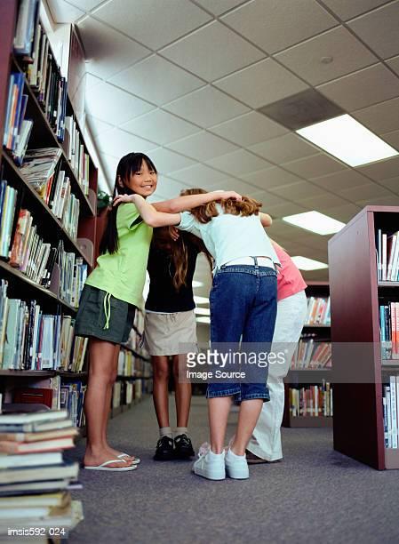 Mädchen umarmen in der Bibliothek