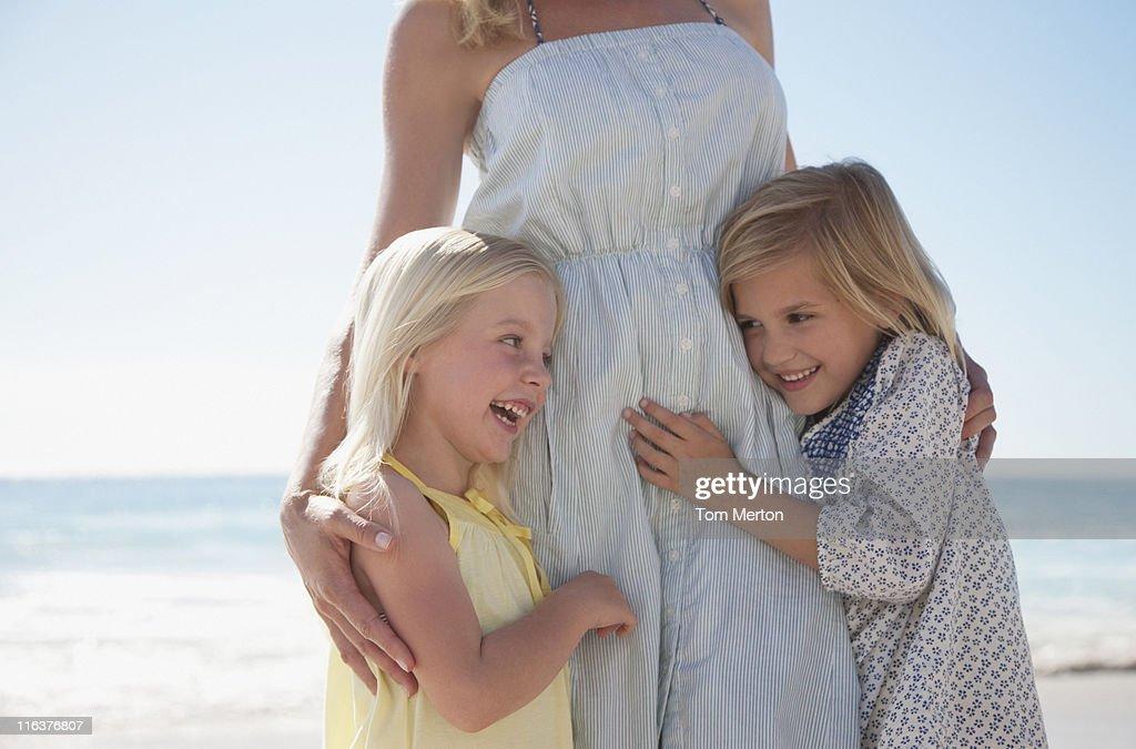 Girls hugging mother on beach : Stock Photo