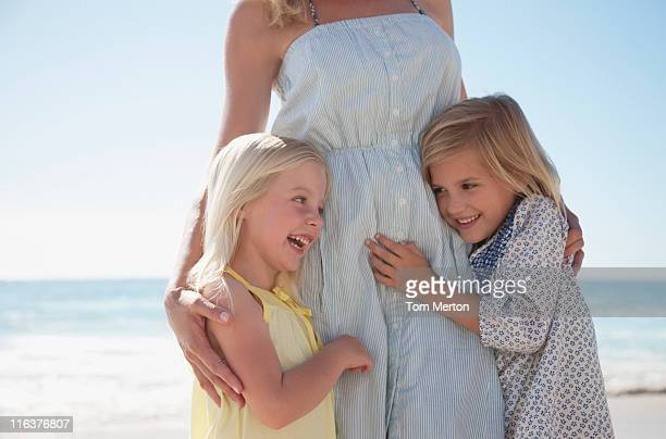girls hugging mother on beach - mid section stock photos and pictures