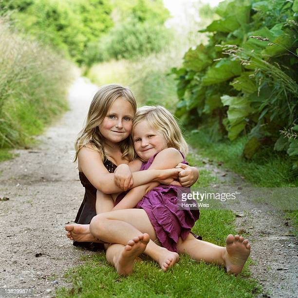 girls hugging on dirt path - northern europe stock pictures, royalty-free photos & images