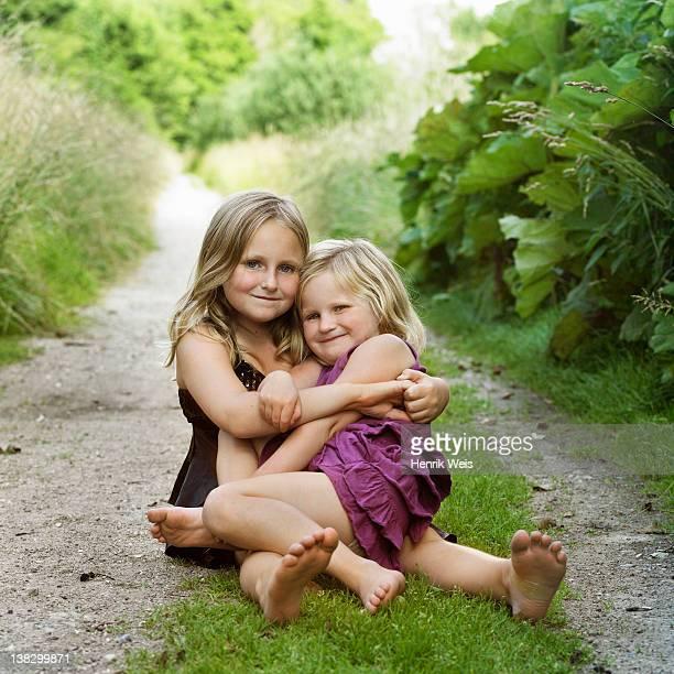 girls hugging on dirt path - noord europa stockfoto's en -beelden