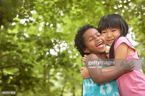 girls hugging outdoors - somente crianças - fotografias e filmes do acervo