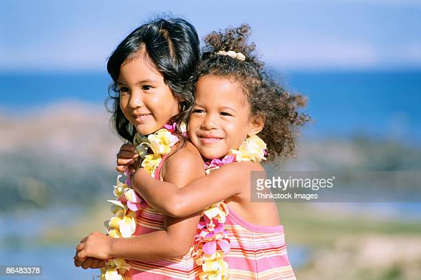 girls hugging - lei day hawaii stock pictures, royalty-free photos & images