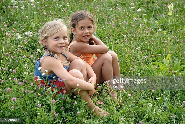 girls in a blooming meadow - young tiny girls stock photos and pictures
