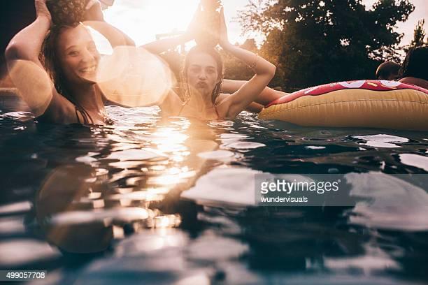 Niñas en una piscina retención pineapples playfully en la cabeza