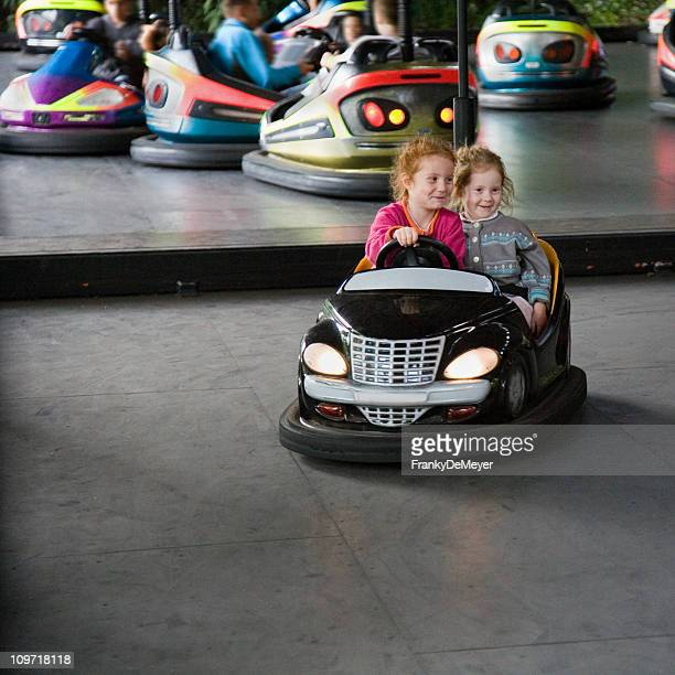 girls in autoscooter at the amusement park - bumpy stock photos and pictures