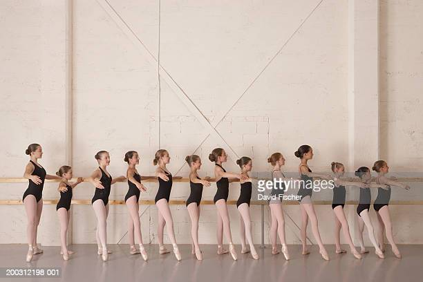 girls (8-13) in ballet class, holding bar in ballet pose, side view - barre class stock photos and pictures