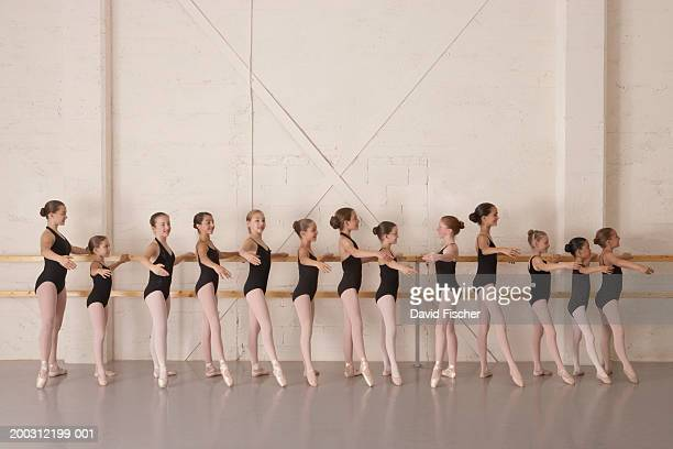 Girls (8-13) in ballet class, holding bar in ballet pose, side view