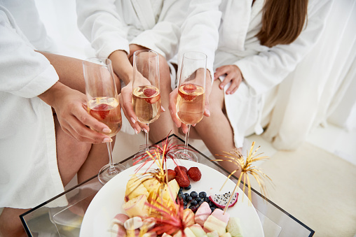 Girls in bathrobes holding glasses of champagne with strawberries 1029862122