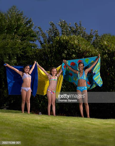 Girls in bikinis (9-10) holding up beach towels, smiling, portrait