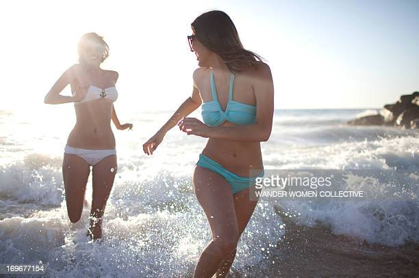 Girls in bikinis running out of waves on beach