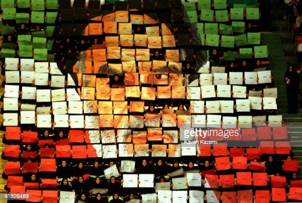 Girls in black uniforms hold up an image mosaic of Ayatollah Khomeini made up of individual boards each in one of the three colors of the Iranian...