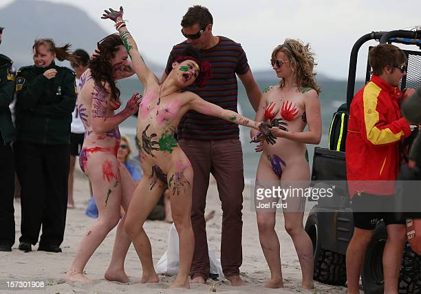 Girls in body paint ham it up with a local radio dj during an attempt to break the skinny dip world record at Papamoa Beach on December 2 2012 in...