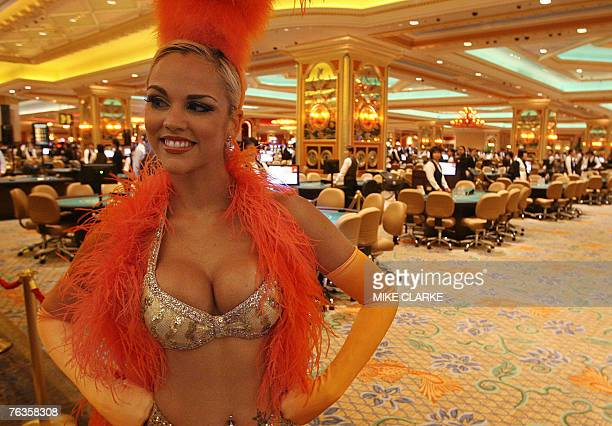 A girls in costume lines the entrance to the casino floor prior to doors opening for the first time at the Venetian in Macau 28 August 2007 The...