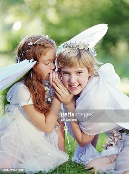Girls (9-12) in costume, one whispering