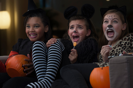 Girls in costumes watching scary movie together on Halloween - gettyimageskorea