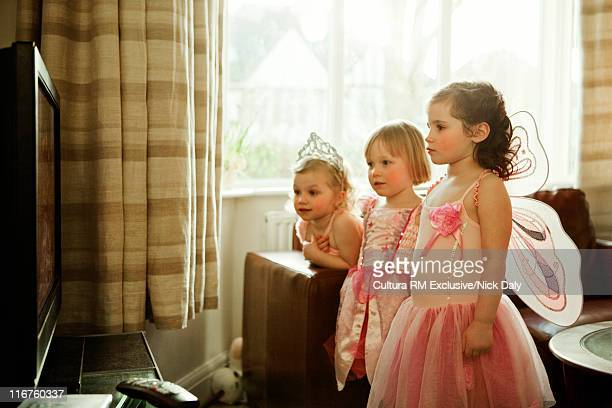 Girls in costumes watching television