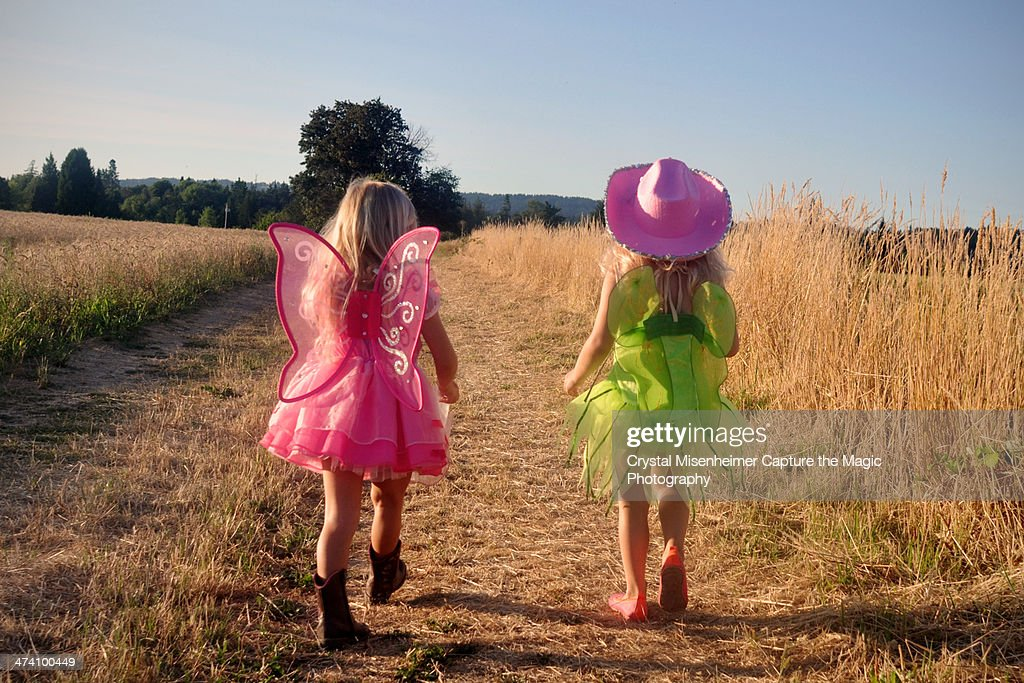 Girls in dress up clothes walking on country road : Stock Photo