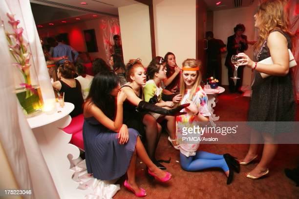 Girls in elegant dresses sitting and talking girl with orange sweatband and tiedye dress kneeling n floor 18th Birthday Party Nobu Metropolitan Hotel...