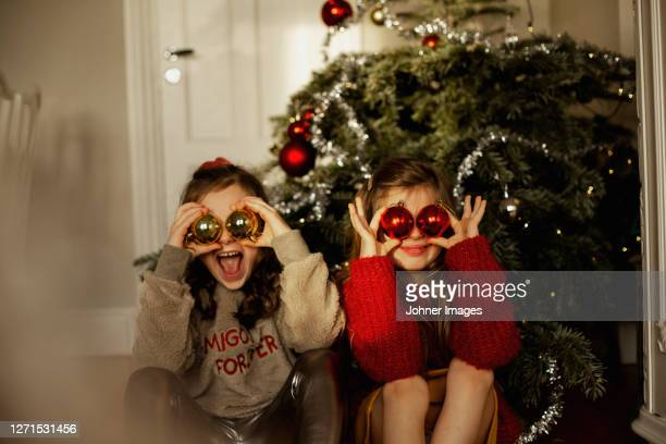 girls in front of christmas tree - mischief stock pictures, royalty-free photos & images
