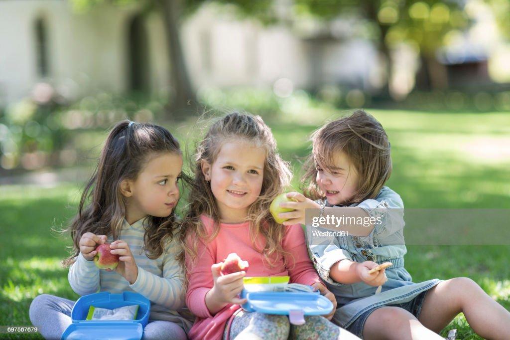 Girls in garden sharing lunch : Stock Photo