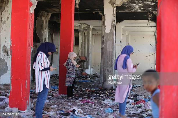 Girls in Gaza on 14 July 2016 playing Pokemon game searching for Pokemon animals and monsters under the rubble of houses destroyed by Israel in the...