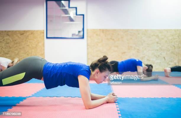 mädchen im fitnessstudio tun planke übung für rückenwirbelsäule - mittlerer teil stock-fotos und bilder