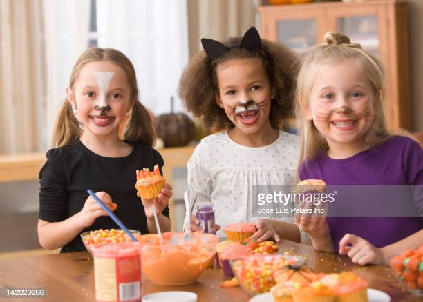 girls in halloween costumes decorating cupcakes - candy corn stock photos and pictures