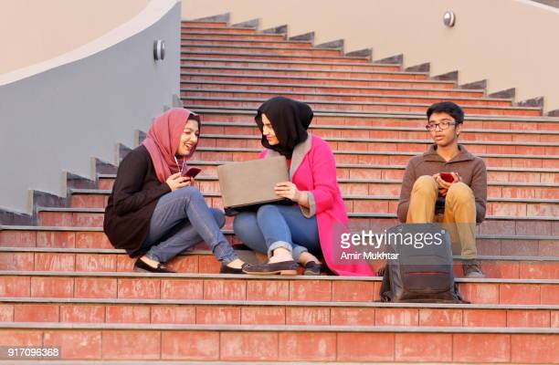 girls in hijab (head scarf) and a young boy enjoying and having leisure time together using laptop and cell phones. - punjabi girls images stock photos and pictures