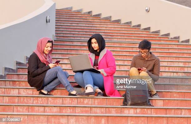 girls in hijab (head scarf) and a young boy enjoying and having leisure time together using laptop and cell phones. - pakistan girl stock photos and pictures