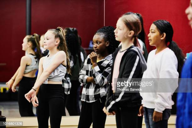 Girls in hip hop dance group watching teammate perform during practice in dance studio