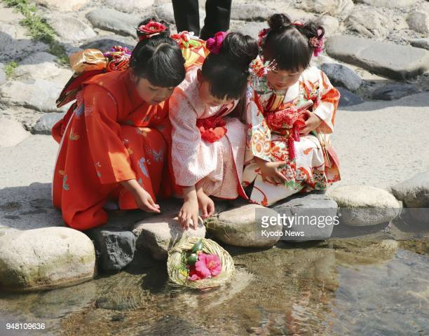 Girls in kimono float a flower on the Sendai River in Tottori western Japan on April 18 the day according to the lunar calendar corresponding to the...