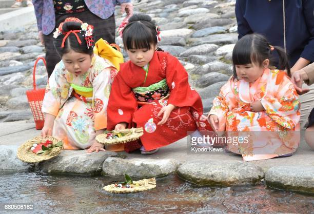 Girls in kimono set papermade Hina dolls placed on small straw boats afloat on Sendai River in Tottori western Japan on March 30 the day...