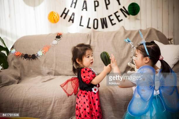 テントウムシの衣装で女の子と女の子の蝶の衣装でヘチマに興味があるように見えます。