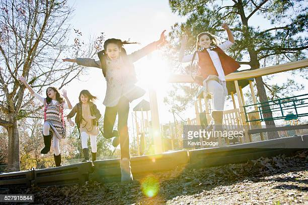 girls (6-9) in playground with lens flare - nur kinder stock-fotos und bilder