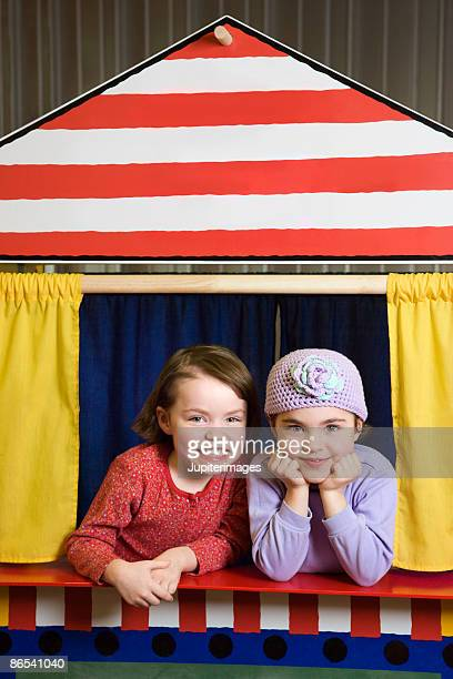 girls in puppet show booth - puppet show stock photos and pictures