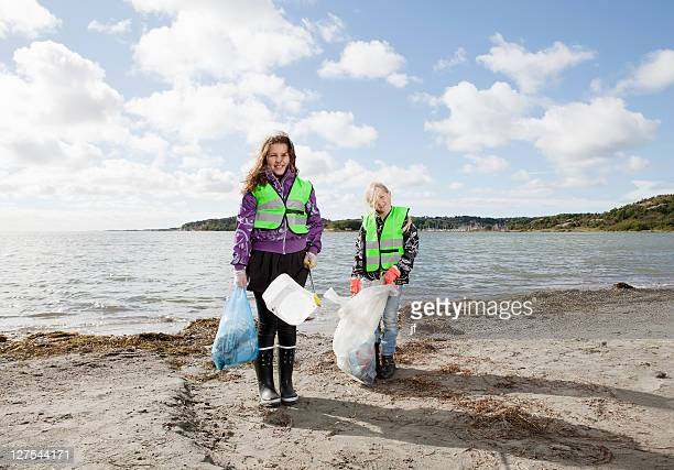 Girls in safety vests cleaning beach