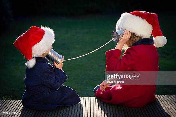 Girls in Santa hats playing with tin can phone