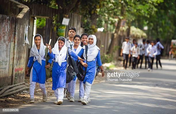 Girls in school uniform walking along a road after school on April 13 2016 in Savar Bangladesh