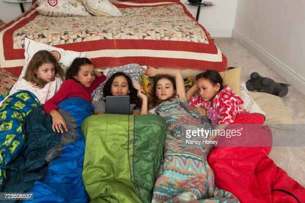 girls in sleeping bags at slumber party using digital tablet - slumber party stock pictures, royalty-free photos & images